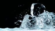 Water splashing against ice cubes, Slow Motion video