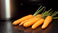 SLOW MOTION: Water stream falls on a carrots on a table in a kitchen video