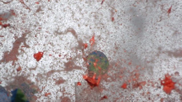 Watermelon painted like earth is shot with gun, slow motion video