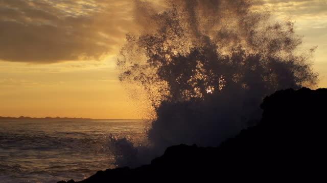 Wave hitting rocks at sunrise video