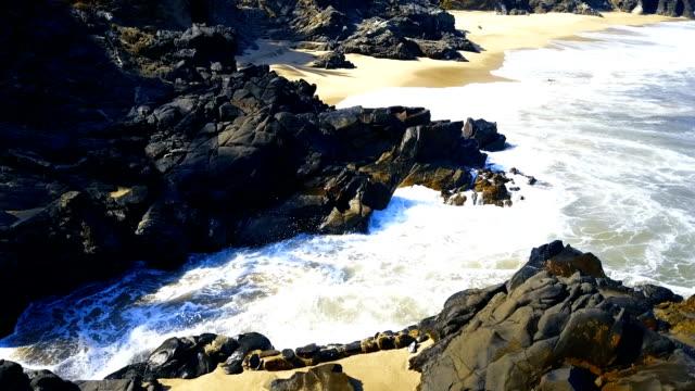 Waves breaking on rocky beach video