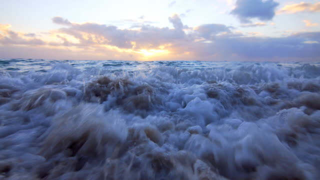 Waves coming onto the sandy beach at sunset video