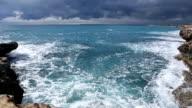 Waves crash against rocky shoreline after storm video