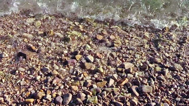 Waves roll over pebbles in sea video