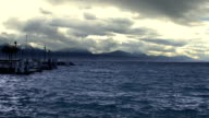 Waves splashing on choppy water surface, stormy cloudscape, mountains on horizon video