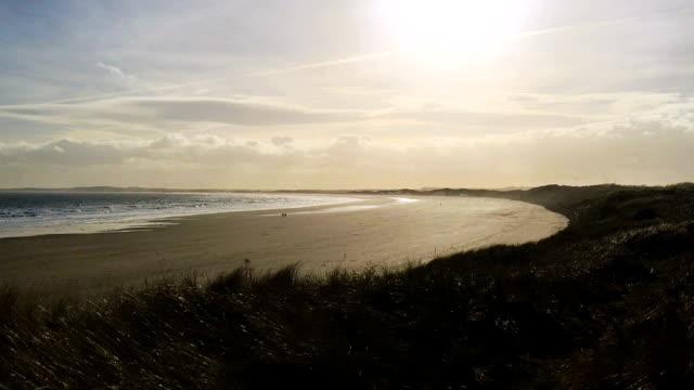 Waves wash across sandy beach as sun sets at twilight video