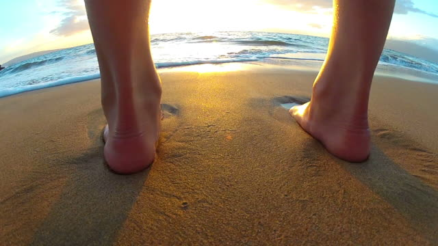 Waves washing over young girls feet at the beach video