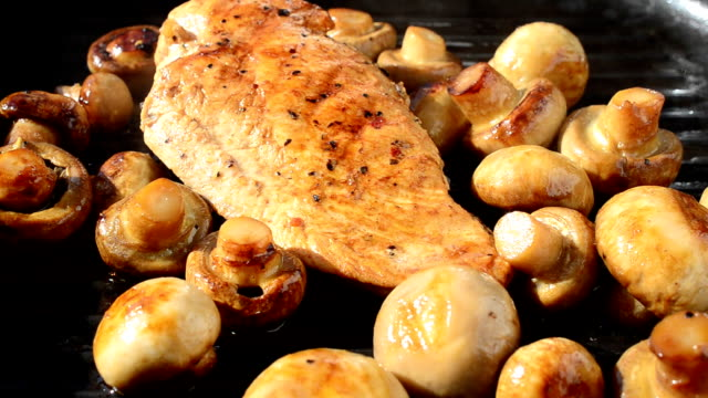 We fry mushrooms with chicken on a grill. video