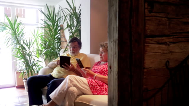 Wealthy senior couple is reading ebook at home video