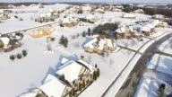 Wealthy suburban homes blanketed in deep winter snow, aerial view video