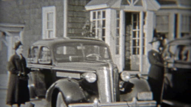 1937: Wealthy suburban women showing off their new cars. video