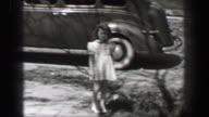1939: Wealthy young girl wavy curly long bangs hair style doll closes car door walks home. video