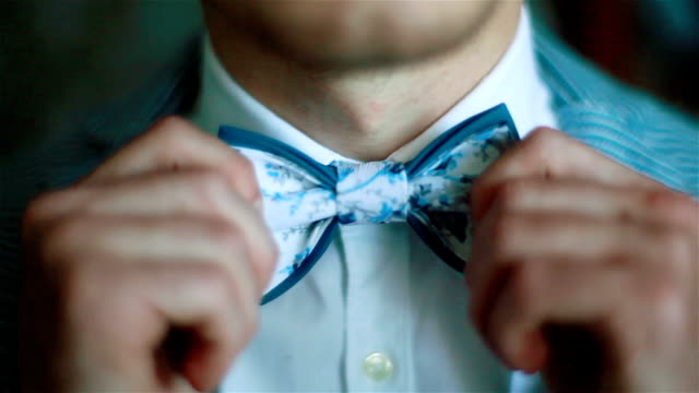 Wearing bow tie close up. Male hands check correct and adjust casual blue bow tie handmade from printed fabrics shallow depth of field. Elegant accessories male fashion macho dandy gentleman concept video