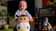 Weary small child is smiling while riding a plush horse video