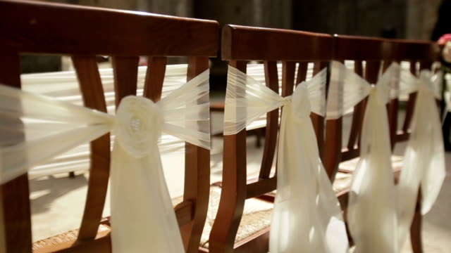 Wedding chairs on the ceremony decorated with white silk bows close up video