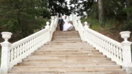 Wedding couple descends the stairs of old park video