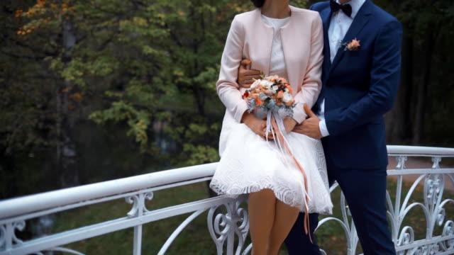 Wedding couple in autumn park on small bridge video
