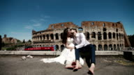 Wedding couple in Rome by Coliseum sitting beside, embracing one another and kissing. Honeymoon in Italy, Europe video