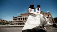 Wedding couple in Rome dancing barefoot at the rooftop near Coliseum, happy groom watches his bride playing with her long wedding dress. Honeymoon in Italy, Europe video