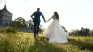 Wedding Couple Runing in grass Field near Castle on Sunset video