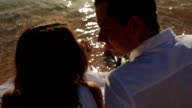 Wedding couple wet their feets in the sea close up video