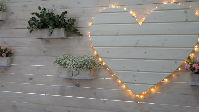 Wedding decor of flowers in a pot and a large white wooden heart video