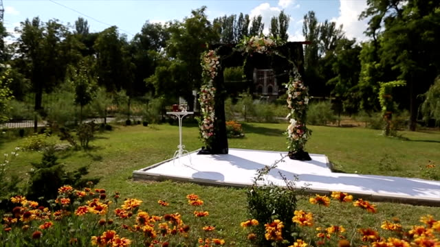 Wedding decorations for outdoor wedding ceremony. Wooden arch decorated with white and pink roses. Bees and bumblebees flying around natural flowers video