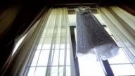 Wedding dress hanging in window video