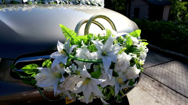 Wedding rings decorated with flowers on car after the rain video