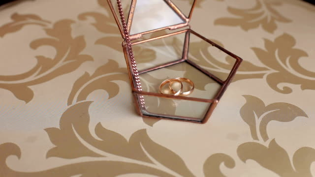 Wedding rings lie in a glass box, close-up. video
