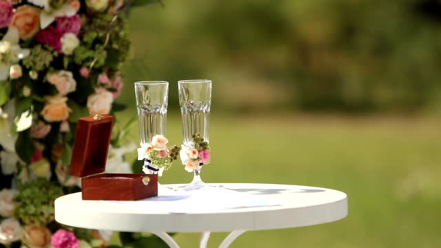 Wedding rings of white gold in the wooden box on the table. Glasses decorated with rorses and berries. Decorations for outdoor ceremony video