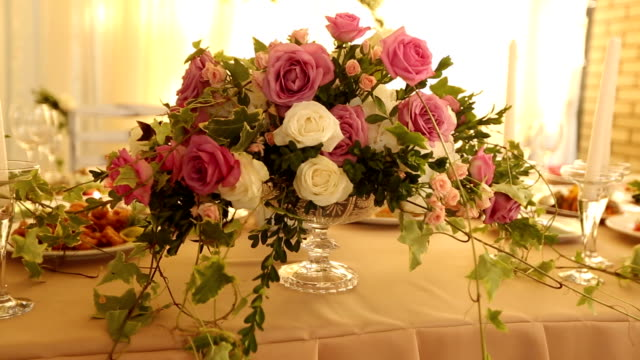 Wedding table rustic style decor with dishes, drinks and flowers in pink and beige colours. Floristic compositions of roses on party banquet dining table video