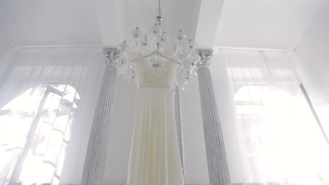 Wedding white dress hanging on chandelier inside space room video
