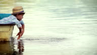 A wee boy sprinkles water all around sitting in the wooden boat in the middle of lake video