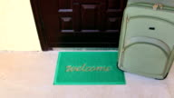 Welcome home door mat with suitcase travel background video