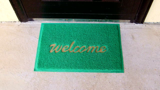 Welcome home mat female traveler with suitcase passes through the front door video