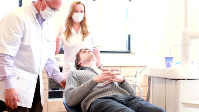 Welcoming patient in the dental office with handshake. video