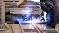 Welder at work in metall factory. Welder welding metal parts video