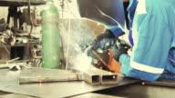 Welder in factory welding steel parts video