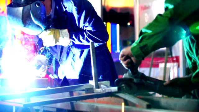 Welding and grinding metal at a factory. video