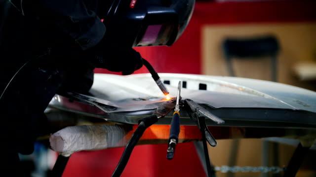 Welding industrial: worker in helmet repair detail in car service video