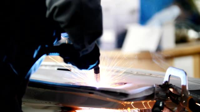 Welding industrial: worker repair detail in car service, close up video
