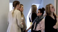 Well-dressed girls stand in corridor and talk with each other video