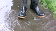 Wellington boots splashing in a muddy puddle video