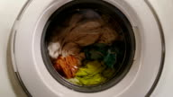 Wet clothes turning in washing machine, view through front glass video