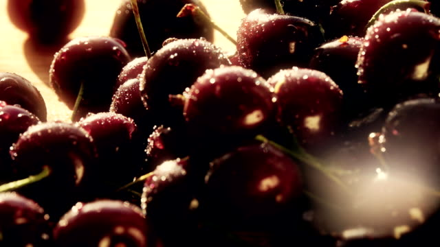Wet ripe sweet cherries on a wooden table on a sunny summer day video