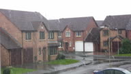 Wet snow falling on street of houses in suburban England video