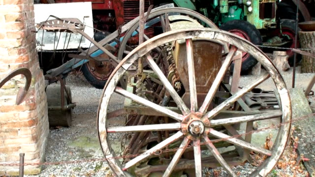 Wheels of old, non functioning agricultural machinery in a medieval italian former farm video