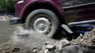 Wheels of SUV car NIVA splashing water crossing creek on the way video