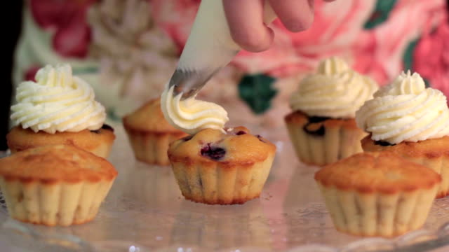 Whipped cream frosting applied to berry cupcakes video
